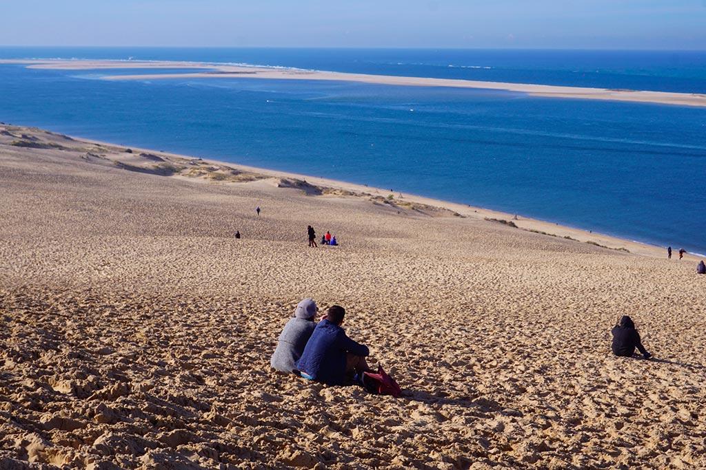 Image de personnes assises sur la dune du pilat, contemplant l'horizon