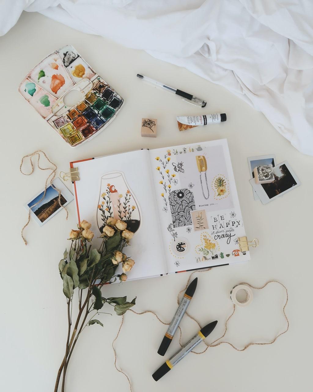 Photographie d'un carnet de voyage entouré de divers accessoires